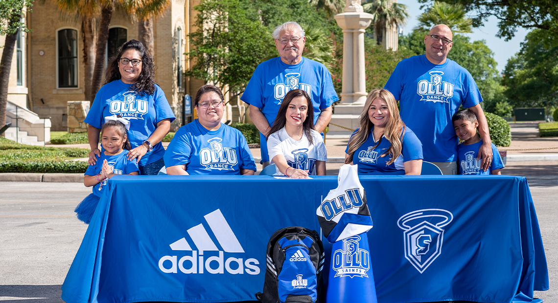 Nadia is pictured with her family and Head Coach Crystal Brock.